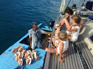 Family choosing conch shells on a BVI Crewed Yacht Charter onboard SY Pacific Wave