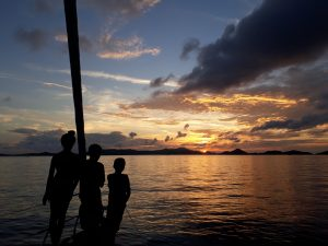 Family onboard Pacific Wave watching the sunset on a BVI Crewed Yacht Charter